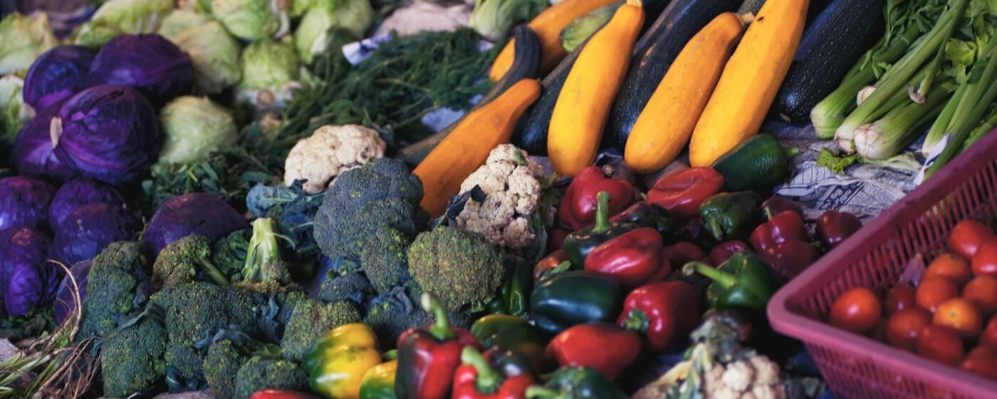 Eine große und bunte Auswahl Gemüse liegt an einem Marktstand aus: unter anderem Zucchini, Paprika und Brokkoli.